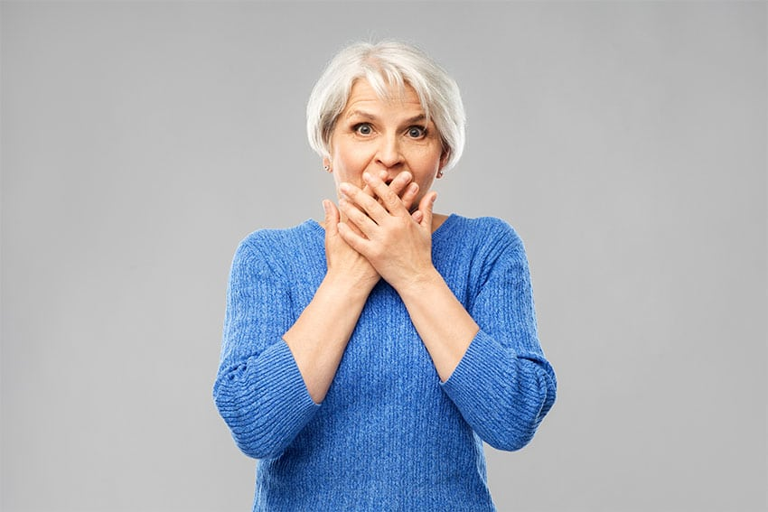 older woman covering her mouth in embarrassment