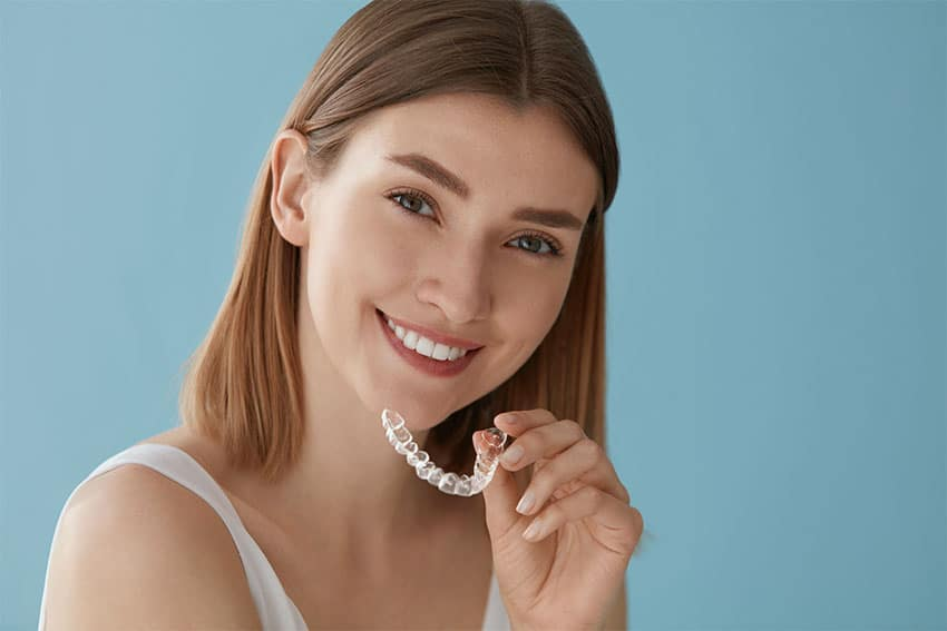 cute young woman placing clear braces on her top teeth